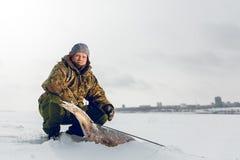 Spearfishing met speargun schoot een grote vis onder het ijs van de rivier Volga Stock Afbeeldingen