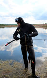 Spearfishing. Underwater hunter in a wetsuit in the lake stock photo
