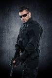 Spec ops police officer SWAT in black uniform studio Stock Photography