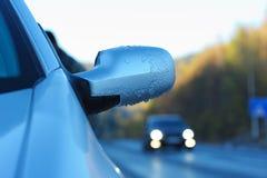 Specchietto retrovisore coperto di ghiaccio dell'automobile contro la strada Fotografia Stock