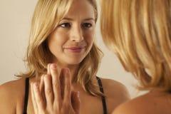 Specchio commovente della donna mentre esaminando riflessione Fotografie Stock Libere da Diritti
