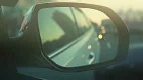 Specchio di automobile sui precedenti dei precedenti vaghi della strada stock footage