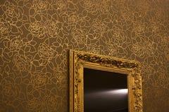 Specchio sulla parete dorata del walpaper Immagini Stock