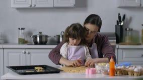 Speciaal behoeftenkind met moeder die koekjes verwijderen stock videobeelden