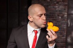 Special agent kissing little toy duck. Contract killer in suit and red tie shows his fears and secrets. Hired murderer wallpaper or background concept royalty free stock photo