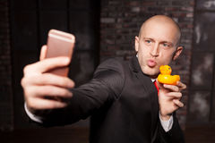 Special agent makes selfie with little toy duck. On phone camera. Contract killer in suit and red tie shows his fears and secrets. Hired murderer wallpaper or stock images