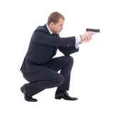 Special agent man in business suit sitting and shooting with gun Stock Photos