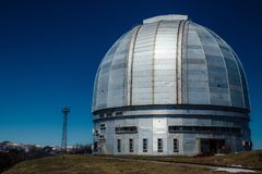 A special astrophysical observatory against the background blue sky and snowy peaks of the Caucasian mountains.  royalty free stock photos
