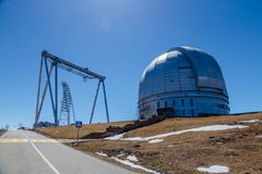 A special astrophysical observatory and a crane against the background of the blue sky.  stock images