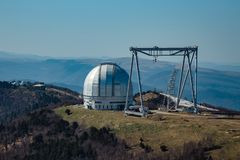 A special astrophysical observatory and a crane against the background of the blue sky and Caucasian mountains.  royalty free stock images