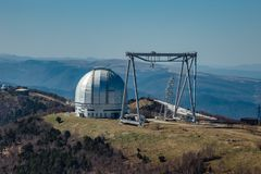 A special astrophysical observatory and a crane against the background of the blue sky and Caucasian mountains.  royalty free stock photo