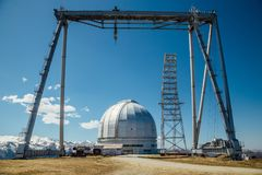 A special astrophysical observatory and a crane against the background of the blue sky and snowy peaks of the Caucasian mountains.  royalty free stock photography