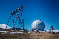 A special astrophysical observatory and a crane against the background of the blue sky and snowy peaks of the Caucasian mountains.  royalty free stock images