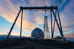 A special astrophysical observatory and a crane against the background of the sunset sky. And snowy peaks of the Caucasian mountains stock photography