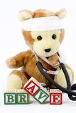 A Special Courage. A stuffed bear wears a real stethoscope around its neck, has his arm in a sling, and has gauze wrapped around his head to display a special Royalty Free Stock Images