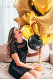Special day amused laughing brunette girl balloons. Special day. Amused brunette girl sitting on sofa in black sequin mini dress, laughing, holding bunch of royalty free stock photo