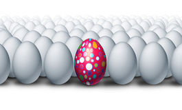 Special Decorated Egg. Standing out as a a creative outstanding individual from a group of ordinary white eggs as an Easter celebration symbol for a spring Stock Image