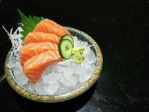 Special Deluxe salmon sashimi set on ice sever with wasabi and cucumber , traditional Japanese food with space, focus salmon. Special Deluxe salmon sashimi set Royalty Free Stock Images