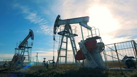 Two oil towers, oil rigs work on a field, close up. Special derricks pump oil on a field stock footage