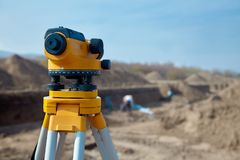 Special device level for surveyor builders, geodesy equipment close up in front of a ground work with people on blurred backgrou royalty free stock image