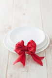 Special dinner  occasion. White plate special dinner  occasion with someone special red bow present Royalty Free Stock Images