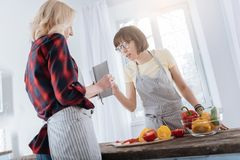 Nice smart woman looking at the recipe. Special dish. Nice pleasant smart women standing at the table and looking at the recipe while cooking a special dish Royalty Free Stock Photography