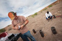 Special Effects Team Working. Two special effects workers setting up pyrotechnics in desert Royalty Free Stock Photography