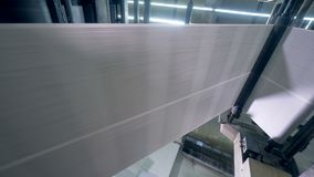 Long newspaper sheet going on a print office line, bottom view. Special equipment moving long paper sheet