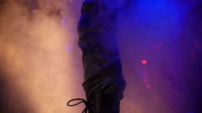 Special equipment produces smoke in slow-mo from under the feet of one of the musicians rock. Rock concert. Special equipment produces smoke in slow-mo from stock footage
