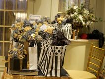 Special event party gift table. Elaborate black and white gifts with gold ribbons on hall table near glass doors Royalty Free Stock Image
