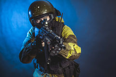 Special force. The man in the image of a member of the special forces division with assault rifle in blue light. Russian police special force - Special Rapid stock photos
