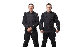 Special force troops with gun and baton. Special force troops with a gun and a baton in black uniform and body armor on white background. Two police officers in stock photography