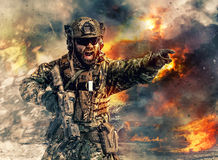 Special forces in action. Bearded soldier of special forces in action pointing target and giving attack direction. Burnt ruins, Heavy explosions, gunfire and Royalty Free Stock Images