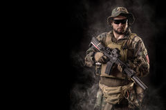Special forces operator with rifle. Special Forces soldier with an assault rifle on a black background Stock Image
