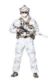 Special forces operator in winter camo clothes. Special forces operator of Navy Seals armed with assault rifle with closed face in polarized sunglasses and Royalty Free Stock Images