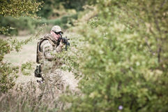 Special forces on patrol. Special forces soldier during assault on the battlefield Stock Photos