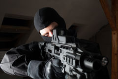 Special forces soldier is aiming and shooting on the target. Special forces soldier/policeman is aiming and shooting on the target during the night strike in a Royalty Free Stock Photography