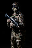 Special forces soldier in camouflage with rifle. Special forces soldier in camouflage,mask and helmet with rifle on black background royalty free stock images