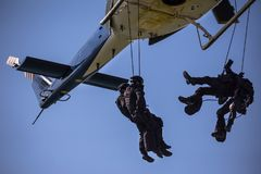 Special forces team helicopter rope jump. Unmarked and unrecognizable swat team stock photography