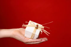 Special gift for you. Handing a small gift tied with raffia and decorated with red and gold beads against a red background - suitable for Christmas, valentine or Royalty Free Stock Image