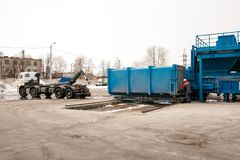A special heavy machine loads a container with sorted waste. stock photo