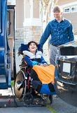 Special needs boy in wheelchair on vehicle handicap lift stock images
