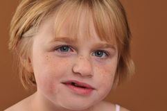 Special needs girl. Isolated against a brown background royalty free stock photo