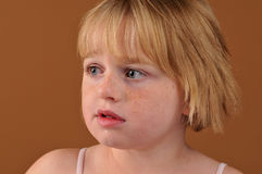 Special needs girl. Isolated against a brown background stock photography
