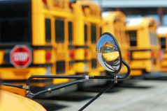 A special needs school bus` reflection in its own mirror with the big ones in the background. Stock Image