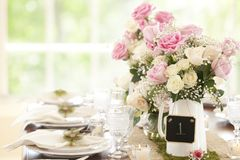 Special occasion dining table setting with beautiful roses bouquet. Special occasion dining table setting with place card Stock Images