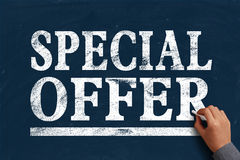 Special Offer. Hand with chalk is writing the text Special Offer on the blue chalkboard Stock Image