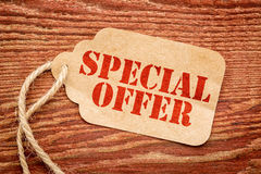 Special offer on a price tag. Special offer sign a paper price tag against rustic red painted barn wood Stock Images