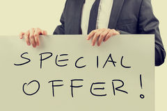 Special offer signboard. Retro effect faded and toned image of a businessman holding a handwritten  Special offer promotion signboard Royalty Free Stock Photos