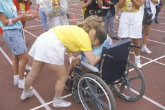 Special Olympics athlete in wheelchair, crossing finish line, being congratulated, UCLA, CA Stock Photo